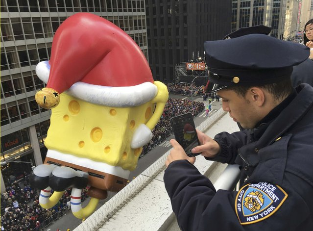A New York Police Department officer takes a photo with his cellphone of a holiday-season themed float above 6th Ave during the 89th Macy's Thanksgiving Day Parade in the Manhattan borough of New York November 26, 2015. (Photo by Carlo Allegri/Reuters)