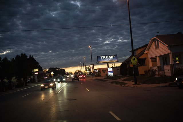 In this October 31, 2020, file photo, a billboard for President Donald Trump is illuminated along a street in Kenosha, Wis. (Photo by Wong Maye-E/AP Photo/File)
