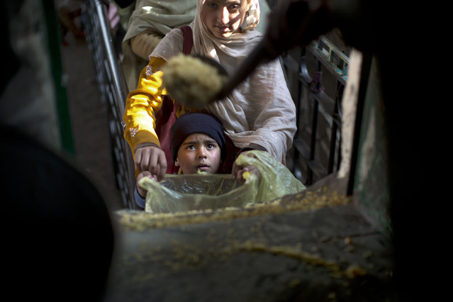 A Pakistani boy holds a plastic bag as he waits to receive rice during a donated food distribution at a shrine in Islamabad, Pakistan, Monday, December 29, 2014. (Photo by Muhammed Muheisen/AP Photo)