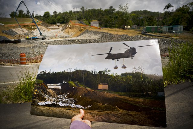 A printed photo taken on October 17, 2017 showing a U.S. army helicopter transporting material to repair the Guajataca Dam, which was damaged during Hurricane Maria, is shown in front of the same location where repairs continue in Quebradillas, Puerto Rico, May 31, 2018. The 345-yard (316-meter) dam, which was built around 1928, holds back a manmade lake covering about 2 square miles (5 square kilometers). (Photo by Ramon Espinosa/AP Photo)