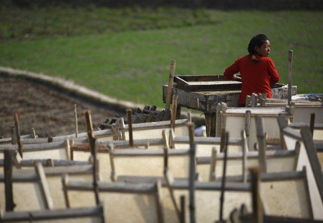 A woman works to create handmade Nepali Lokta paper in Kathmandu January 7, 2015. (Photo by Navesh Chitrakar/Reuters)