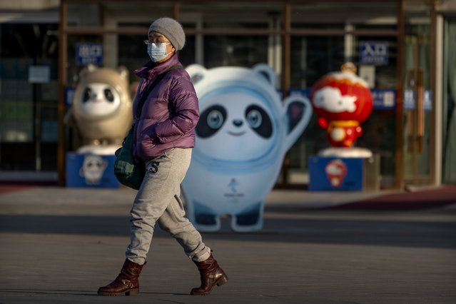 """A woman wearing a face mask to protect against the spread of the coronavirus walks past statues of the 2022 Beijing Winter Olympics and Paralympics mascots on the Olympic Green in Beijing, Tuesday, February 2, 2021. The 2022 Beijing Winter Olympics will open a year from now. Most of the venues have been completed as the Chinese capital becomes the first city to hold both the Winter and Summer Olympics. Beijing held the 2008 Summer Olympics. But these Olympics are presenting some major problems. They are already scarred by accusations of rights abuses including """"genocide"""" against more than 1 million Uighurs and other Muslim ethnic groups in western China. (Photo by Mark Schiefelbein/AP Photo)"""