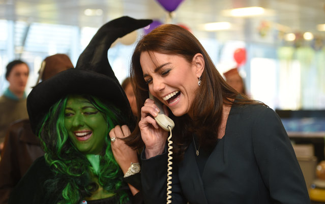 Kate Duchess of Cambridge laughs on the phone as a trader in fancy dress looks on  as the Duches attends ICAP's 23rd annual Charity Day in London Wednesday December 9, 2015. The Duchess and Prince William  joined  ICAP' s brokers to raise revenues from trading on ICAP's charity day that will be donated to a range of charities, including SkillForce, of which William is patron, and SportsAid and Place2Be, of which Kate is patron.  (Photo by Jeremy Selwyn, Pool via AP Photo)