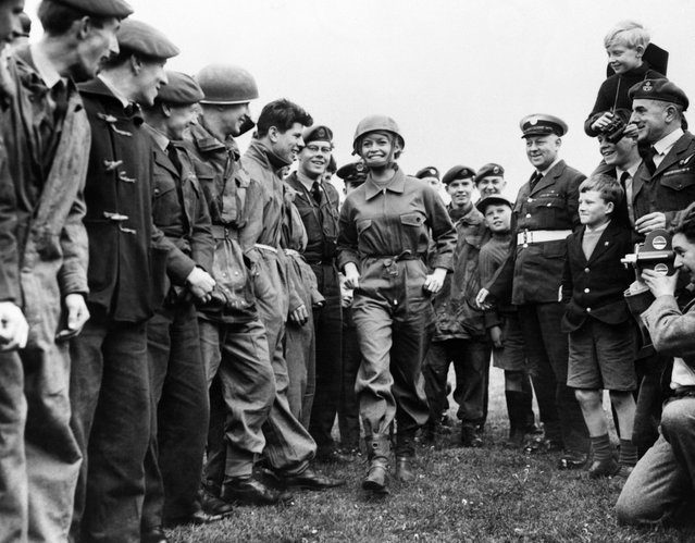 "A photo taken on April 12, 1959 in London shows French actress Brigitte Bardot, flanked by Royal Air Force boys, arriving at the R.A.F. Base on the set of ""Babette s'en va t'en Guerre"" (""Babette Goes to War"") directed by Christian Jaque. (Photo by AFP Photo)"