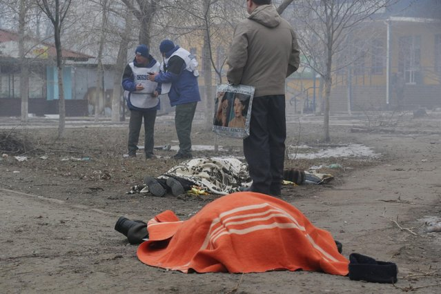 Two dead bodies lay on the ground in a residential area in Mariupol, Ukraine, OSCE members in the background, Saturday, January 24, 2015. A crowded open-air market in Ukraine's strategically important coastal city of Mariupol came under rocket fire Saturday morning, killing at least 10 people, regional police said.(AP Photo/Sergey Vaganov)