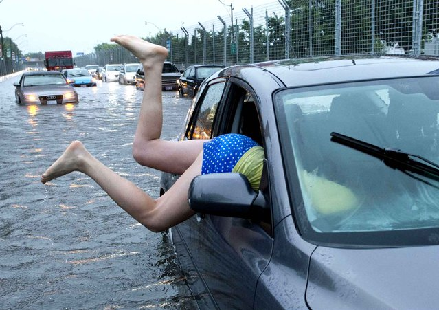 Heavy rains have knocked out power for hundreds of thousands of residents across the Greater Toronto Area, including the majority of Mississauga, and so badly flooded some roads and major highways that drivers abandoned their waterlogged vehicles, on July 8, 2013. (Photo by Frank Gunn/AP Photo)