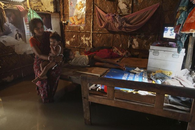 An Indian girl watches television as her mother sits with her sister on a bed inside a waterlogged rented house in Gauhati, India, Tuesday, July 16, 2013. (Photo by Anupam Nath/AP Photo)
