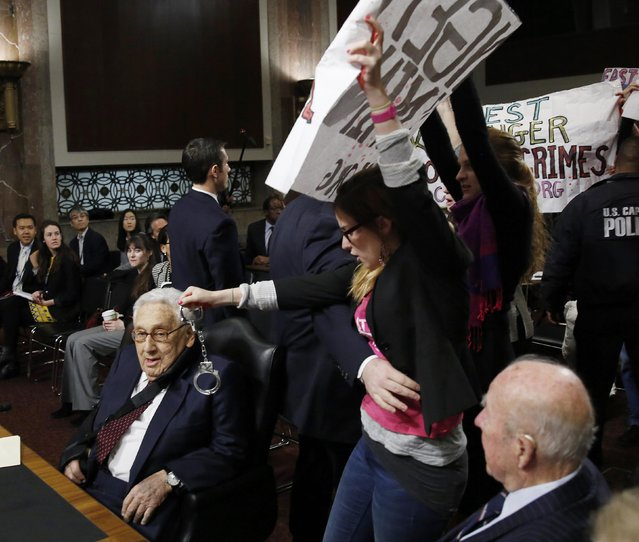 Code Pink demonstrators surround former United States Secretaries of State Henry Kissinger (L) and George Shultz (R) before the beginning of the Senate Armed Services Committee on global challenges and U.S. national security strategy on Capitol Hill in Washington January 29, 2015. (Photo by Gary Cameron/Reuters)