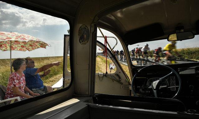 As seen from a spectators' car on the side of the route, a fan (L) points to Belgium' s Greg Van Avermaet (R), wearing the overall leader' s yellow jersey, cycling past during the seventh stage of the 105 th edition of the Tour de France cycling race between Fougeres and Chartres, western France, on July 13, 2018. (Photo by Marco Bertorello/AFP Photo)