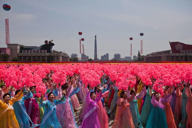 North Korean women wave to their leader Kim Jong Un during a mass military parade on Kim Il Sung Square in Pyongyang to mark the 60th anniversary of the Korean War armistice, Saturday, July 27, 2013. (Photo by David Guttenfelder/AP Photo)