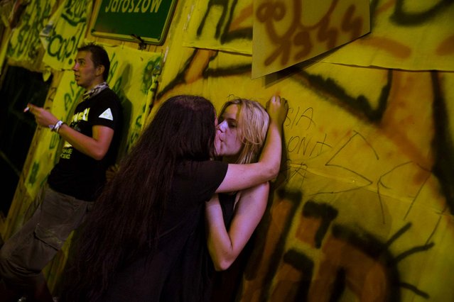 People kiss in front of the central stage at the Woodstock Festival in Kostrzyn-upon-Odra River, close to the Polish-German border, on August 2, 2013. (Photo by Thomas Peter/Reuters)