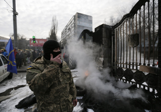 """Volunteers of the """"Aidar"""" battalion burn tires in front of the Ministry of Defense as they protest against a decision to change the leadership of the battalion in Kiev, Ukraine, Monday, February 2, 2015. The """"Aidar"""" battalion, a volunteer force, and the Defense Minister have agreed that the battalion will be divided into two units. (Photo by Sergei Chuzavkov/AP Photo)"""