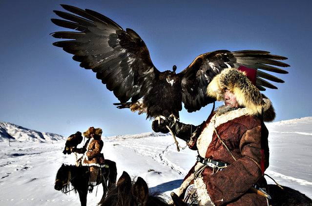 Chinese Kazakh eagle hunters sit on horseback as they travel to a local competition on January 29, 2015 in the mountains of Qinghe County, Xinjiang, northwestern China. The festival, organised by the local hunting community, is part of an effort to promote and grow traditional hunting practices for new generations in the mountainous region of western China that borders Kazakhstan, Russia and Mongolia. (Photo by Kevin Frayer/Getty Images)