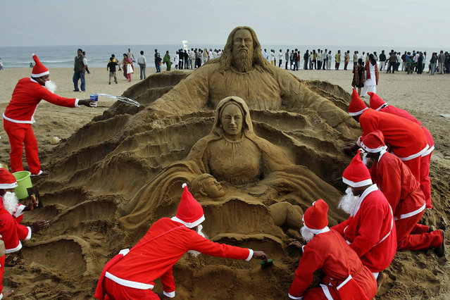 Artists dressed as Santa Claus create a Santa Claus sculpture on the eve of Christmas Puri golden beach, 67 kilometers (42 miles) from the eastern city of Bhubaneswar, India, Saturday, December 24, 2011. Christmas Day is observed as a national holiday in India. (Photo by Biswaranjan Rout/AP Photo)