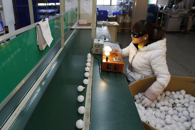 An employee tests newly-made light bulbs along a production line of a factory in Jiaxing, Zhejiang province February 6, 2015. (Photo by William Hong/Reuters)