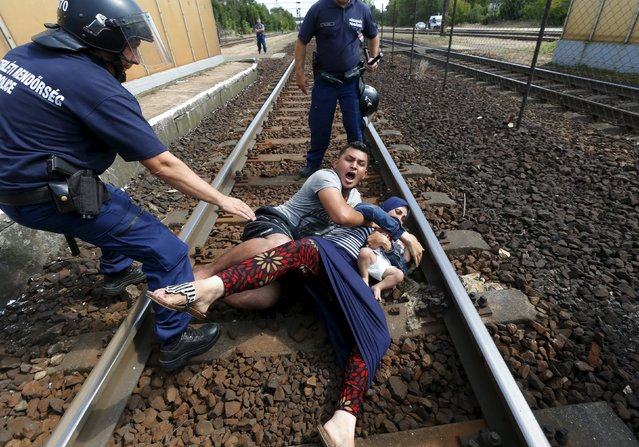 Hungarian policemen stand by the family of migrants as they want to run away at the railway station in the town of Bicske, Hungary, September 3, 2015. (Photo by Laszlo Balogh/Reuters)