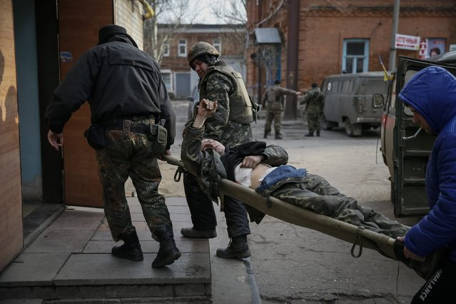 Ukrainian servicemen carry a wounded comrade into a hospital in Artemivsk February 8, 2015. (Photo by Gleb Garanich/Reuters)