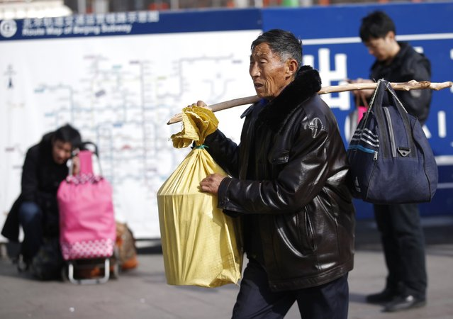 A man carries his belongings with a stick at a railway station in Beijing February 16, 2015. (Photo by Kim Kyung-Hoon/Reuters)