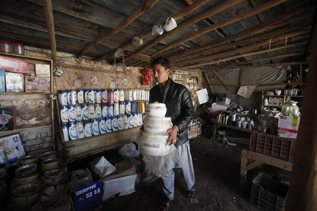 An Afghan refugee boy Wahid, whose family have a residency card which will expire on December 2015, sets up items for sell at his makeshift shop on the outskirts of Peshawar February 18, 2015. (Photo by Fayaz Aziz/Reuters)