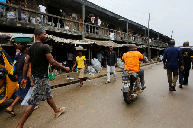 People walk on a street in Araria market in Aba, Nigeria August 19, 2016. (Photo by Afolabi Sotunde/Reuters)