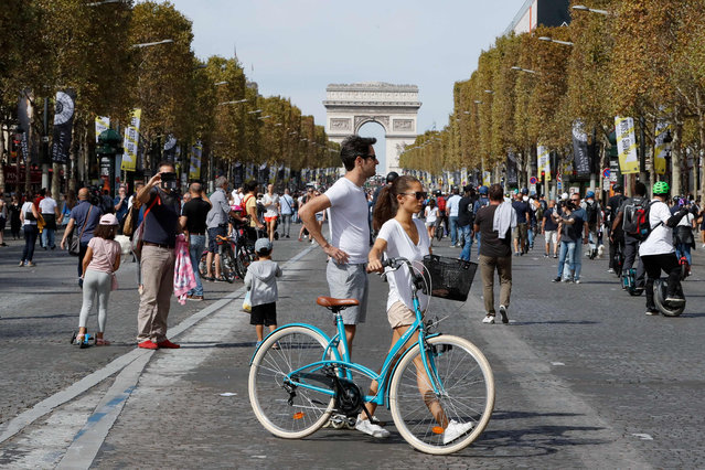 People ride bicycles, monowheel and walk as they enjoy a vehicle- free day in front of the Arc de Triomphe (Triumphal arch) in Paris, on September 16, 2018. Europe should hold an annual car- free day in a bid to ease air pollution, the mayors of Paris and Brussels said on September 15, 2018 on the eve of a vehicle- free day in their cities. (Photo by Francois Guillot/AFP Photo)