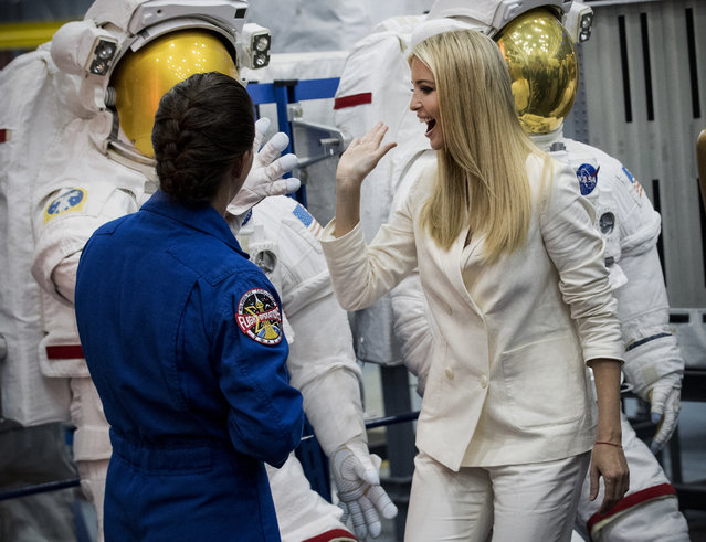 Ivanka Trump high fives a space suit as astronaut Nicole Mann gives her a tour of the Space Vehicle Mockup Facility during a visit to NASA's Johnson Space Center on Thursday, September 20, 2018, in Houston. (Photo by Brett Coomer/Houston Chronicle via AP Photo)