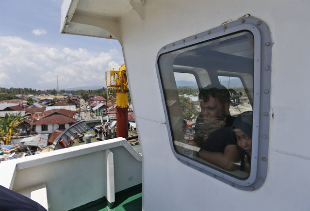 In this Thursday, October 4, 2018, photo, crew members look out of the window from the bridge of Sabuk Nusantara 39 which was swept ashore by the tsunami in Wani village on the outskirt of Palu, Central Sulawesi, Indonesia Indonesia. A week after the magnitude 7.5 quake and tsunami hit central Sulawesi, the crew of the ferry remain on board, waiting for an assessment team to arrive and decide if the ship, its propeller jutting out over the waterfront, could be put back to sea. (Photo by Dita Alangkara/AP Photo)