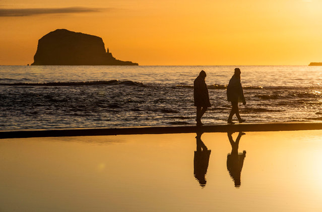 A couple walk along the beach at North Berwick, East Lothian, United Kingdom at sunrise on Thursday, April 15, 2021. (Photo by Jane Barlow/PA Images via Getty Images)