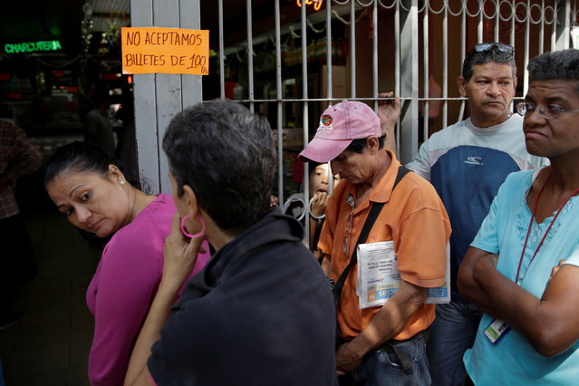 "People queue to deposit their 100 bolivar notes, near Venezuela's Central Bank in Caracas, Venezuela December 16, 2016. The placard reads: ""We do not accept 100 bolivar notes"". (Photo by Marco Bello/Reuters)"