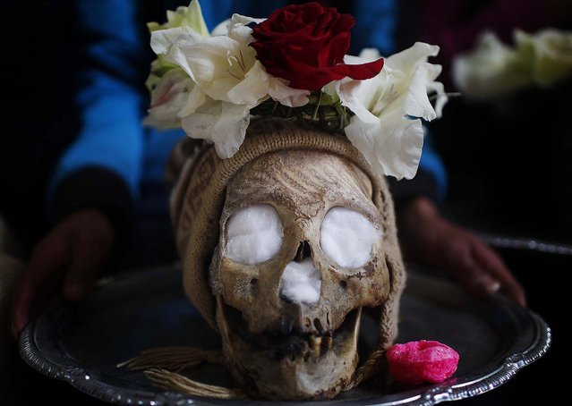A man carries a decorated human skull  on a silver-colored tray. (Photo by Juan Karita/Associated Press)