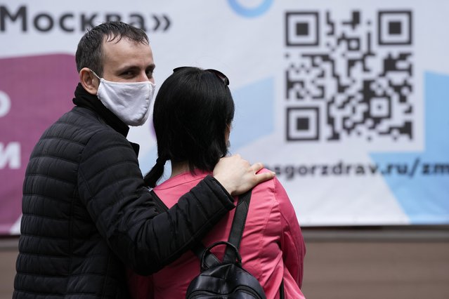 A couple wait in line to receive a coronavirus vaccine at a vaccination center with the sign of a QR code at VDNKh (The Exhibition of Achievements of National Economy) in Moscow, Russia, Friday, July 2, 2021. Russian health authorities on Thursday launched booster coronavirus vaccinations for those who had been immunized more than six months ago, as the country faces a surge in new infections and deaths. (Photo by Alexander Zemlianichenko/AP Photo)