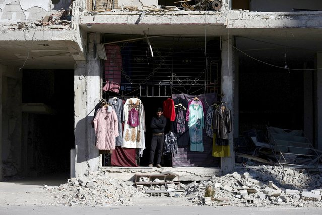 A vendor stands near secondhand clothes displayed for sale in Ain Tarma, in the eastern Damascus suburb of Ghouta, Syria February 4, 2016. (Photo by Bassam Khabieh/Reuters)