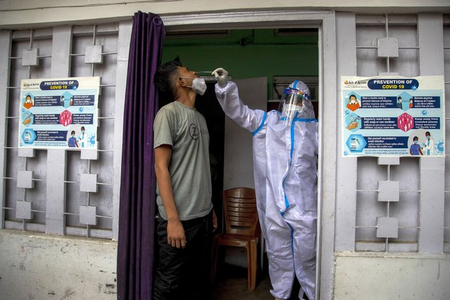 A health worker takes a nasal swab sample to test for COVID-19 in Gauhati, India, Friday, July 16, 2021. (Photo by Anupam Nath/AP Photo)
