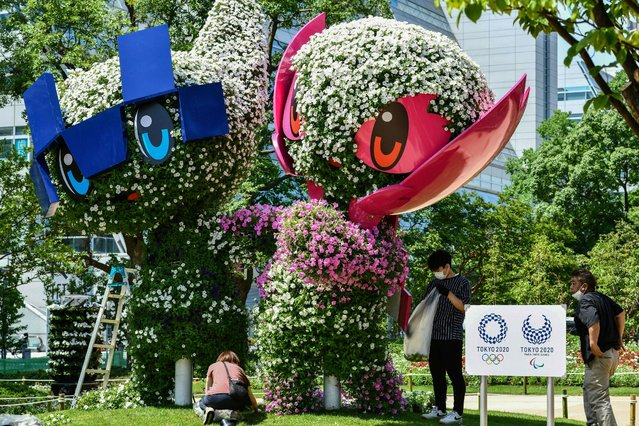 Workers decorate Olympic and Paralympic mascots, Miraitowa (L) and Someity (R), in preparation for the Tokyo 2020 Olympic Games near the main press centre in Tokyo on July 20, 2021. (Photo by Toshifumi Kitamura/AFP Photo)