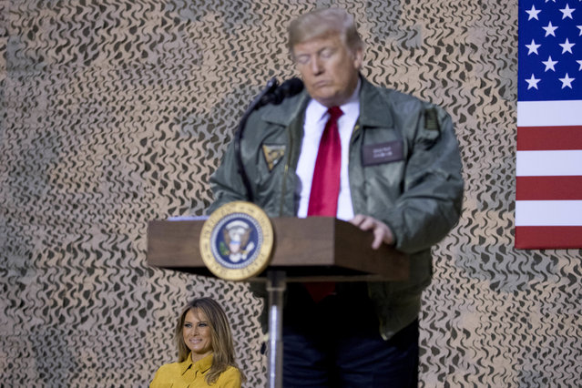 First lady Melania Trump, left, is seated on stage as President Donald Trump pauses as he speaks at a hanger rally at Al Asad Air Base, Iraq, Wednesday, December 26, 2018. In a surprise trip to Iraq, President Donald Trump on Wednesday defended his decision to withdraw U.S. forces from Syria where they have been helping battle Islamic State militants. (Photo by Andrew Harnik/AP Photo)