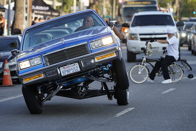 A Lowrider rides on three-wheels on Sunset Blvd., in the Echo Park neighborhood of Los Angeles late Sunday afternoon July 18, 2021. (Photo by Damian Dovarganes/AP Photo)