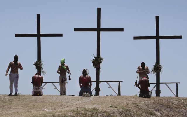 Hooded Filipino penitents flagellate in front of the wooden crosses during Good Friday rituals to atone for sins on April 3, 2015 at Cutud, Pampanga province, northern Philippines. The bizarre ritual is frowned upon by church leaders in this predominantly Roman Catholic country. (AP Photo/Aaron Favila)