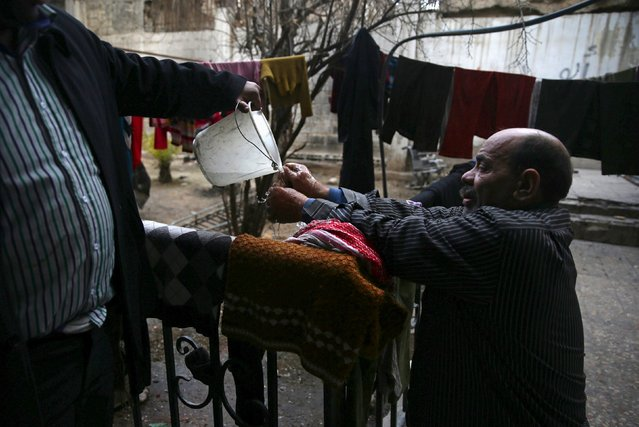 Shahrour, 54, washes his hands at his home in the besieged town of Arbeen, in the Damascus suburbs, Syria February 6, 2016. Shahrour said he developed diabetes at the beginning of the war in Syria. A lack of insulin led to his medical condition worsening and his right foot had to be amputated. Recently he also suffered a stroke that paralysed half his face. He and part of his extended family, a total of 18 people, live together and struggle to get by. (Photo by Bassam Khabieh/Reuters)