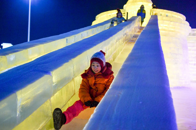 A child plays the ice slide at the Ice-Snow World park in Harbin, capital of northeast China's Heilongjiang Province, January 5, 2017. The theme park which used about 330,000 cubic meters of ice and snow for construction opened on Thursday. (Photo by Xinhua/Barcroft Images)