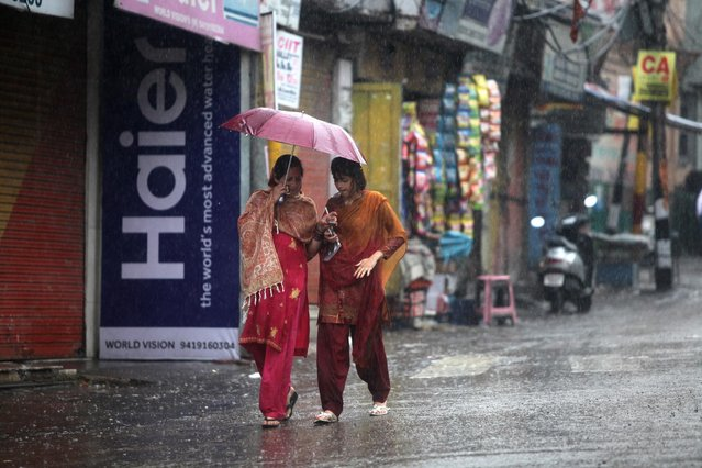 Indian women walk under an umbrella during a spell of unseasonal rain in Jammu, India, Friday, April 3, 2015. (Photo by Channi Anand/AP Photo)