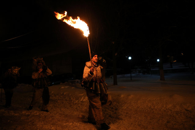"""A man dressed in a costume made of animal fur, called """"kuker"""", carries a torch during a festival in the town of Batanovtsi, Bulgaria January 13, 2017. (Photo by Stoyan Nenov/Reuters)"""