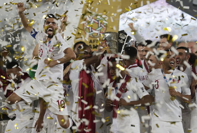 Qatar's forward Hasan Al Haydos, left, celebrates with teammates after winning the the AFC Asian Cup final match between Japan and Qatar in Zayed Sport City in Abu Dhabi, United Arab Emirates, Friday, February 1, 2019. (Photo by Hassan Ammar/AP Photo)