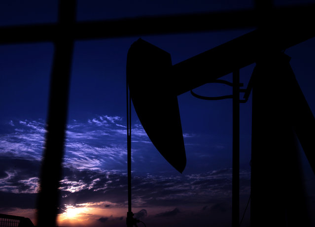 An oil pump operates at sunset Thursday, January 2, 2014, in the desert oil fields of Sakhir, Bahrain. The price of oil fell below $98 a barrel Thursday amid reduced trading volumes and the impact of a strengthening dollar. (Photo by Hasan Jamali/AP Photo)