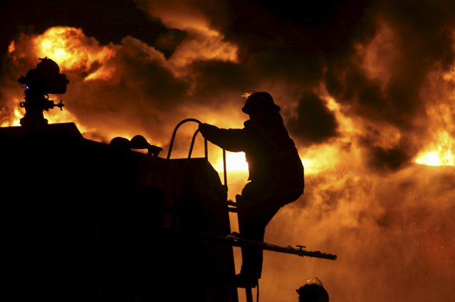 A firefighter climbs onto a fire truck as he and his colleagues try to extinguish a fire at a petrochemical plant in Zhangzhou, Fujian province April 7, 2015. At least six people were injured after an explosion hit part of an oil storage facility on Monday at Dragon Aromatics, Xinhua reported. (Photo by Reuters/Stringer)