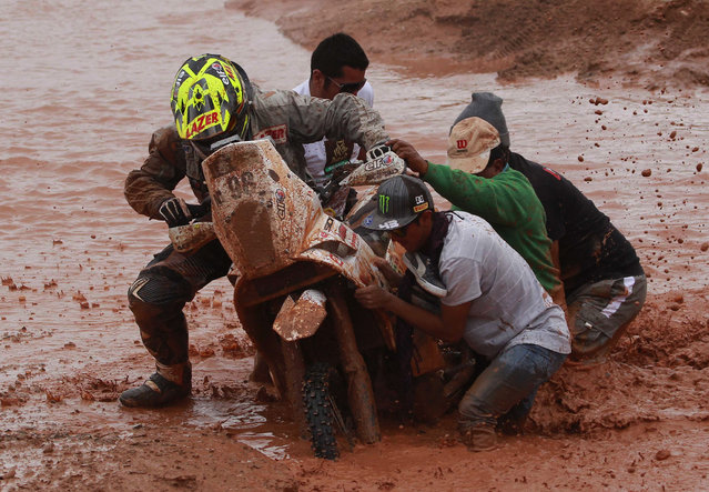 After falling from his motorbike, KTM rider Stephane Hamard of France gets help pushing his bike out of a mud puddle during the seventh stage of the Dakar Rally between the cities of Salta, Argentina and Uyuni, Bolivia, Sunday, January 12, 2014. (Photo by Juan Karita/AP Photo)