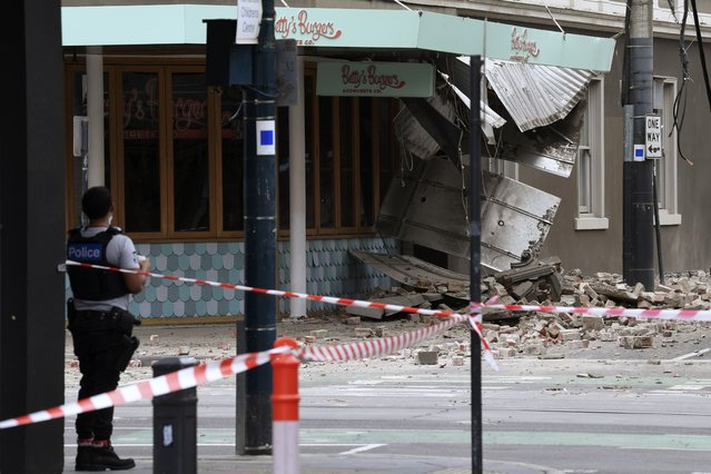 A police officer closes an intersection where debris is scattered in the road after an earthquake damaged a building in Melbourne, Wednesday, September 22, 2021. A magnitude 5.8 earthquake caused damage in the city of Melbourne in an unusually powerful temblor for Australia, Geoscience Australia said. (Photo by James Ross/AAP Image via AP Photo)