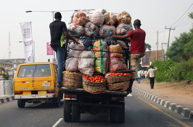 Men hang at the back of a truck loaded with farm produce along a road in Ikeja district in the commercial capital Lagos, Nigeria December 19, 2016. (Photo by Akintunde Akinleye/Reuters)