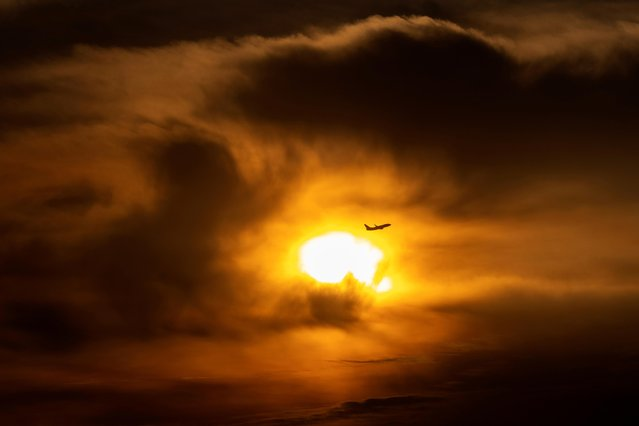 A commercial airliner takes off through clouds during sunrise, near Huntington Beach, California, U.S., October 4, 2021. (Photo by Mike Blake/Reuters)