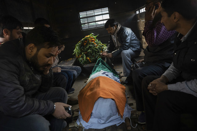 In this Tuesday, December 4, 2018 photo, relatives cry next to the body of police Inspector Subodh Kumar Singh in Chingarwathi, near Bulandshahr, in the northern Indian state of Uttar Pradesh. The previous day, Singh and another person were killed in the mob violence that began with accusations of cow slaughter in the area. (Photo by Bernat Armangue/AP Photo)