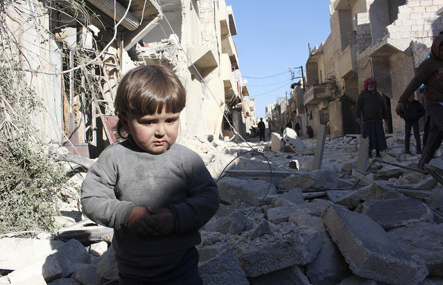 A child is seen amid the rubble of damaged buildings at a site hit by what activists said was a barrel bomb dropped by forces loyal to Syria's President Bashar al-Assad in Masaken Hanano in Aleppo February 13, 2014. (Photo by Mahmoud Hebbo/Reuters)